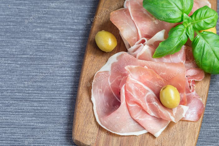 Prosciutto ham on wooden board with basil leaves and green olive