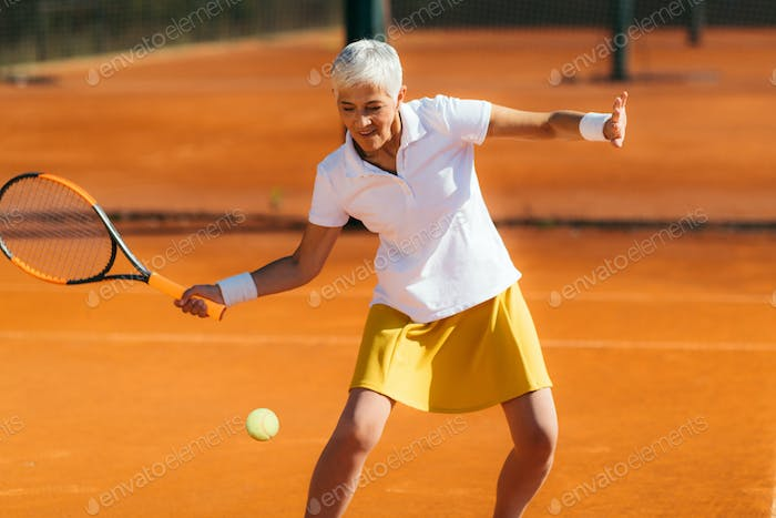 Active Senior Lady in her 60s Playing Recreational Tennis