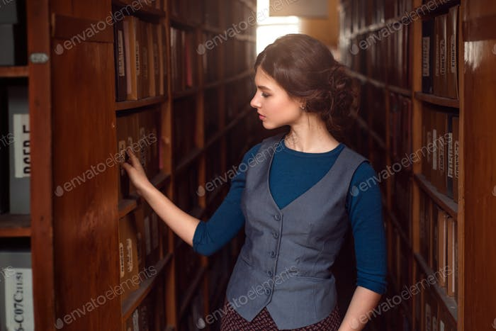 Young woman selecting book from library shelf.