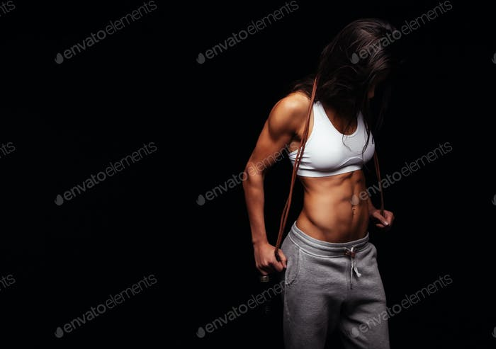 Muscular female posing with jump rope