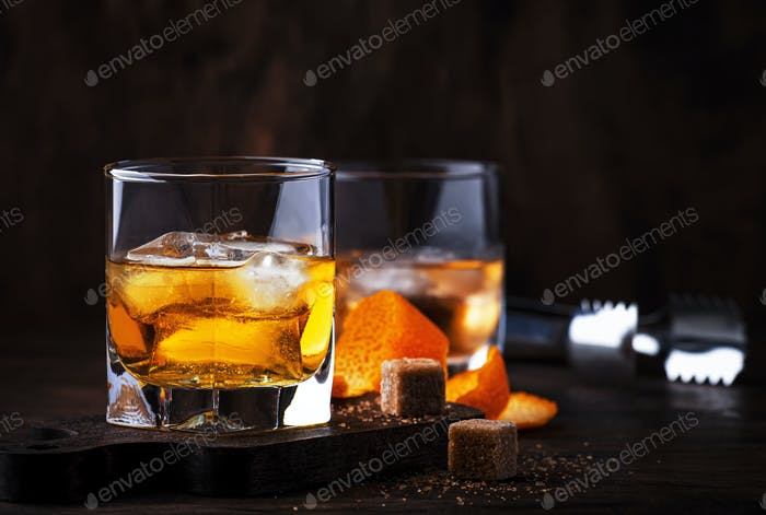 Alcoholic old fashioned cocktail with orange slice, cherry and orange peel garnish