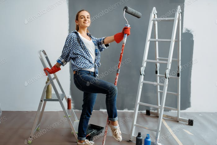Female house painter sitting on a ladder