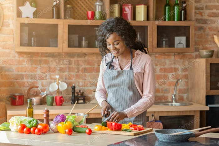 Pretty woman making veggies salad at kitchen