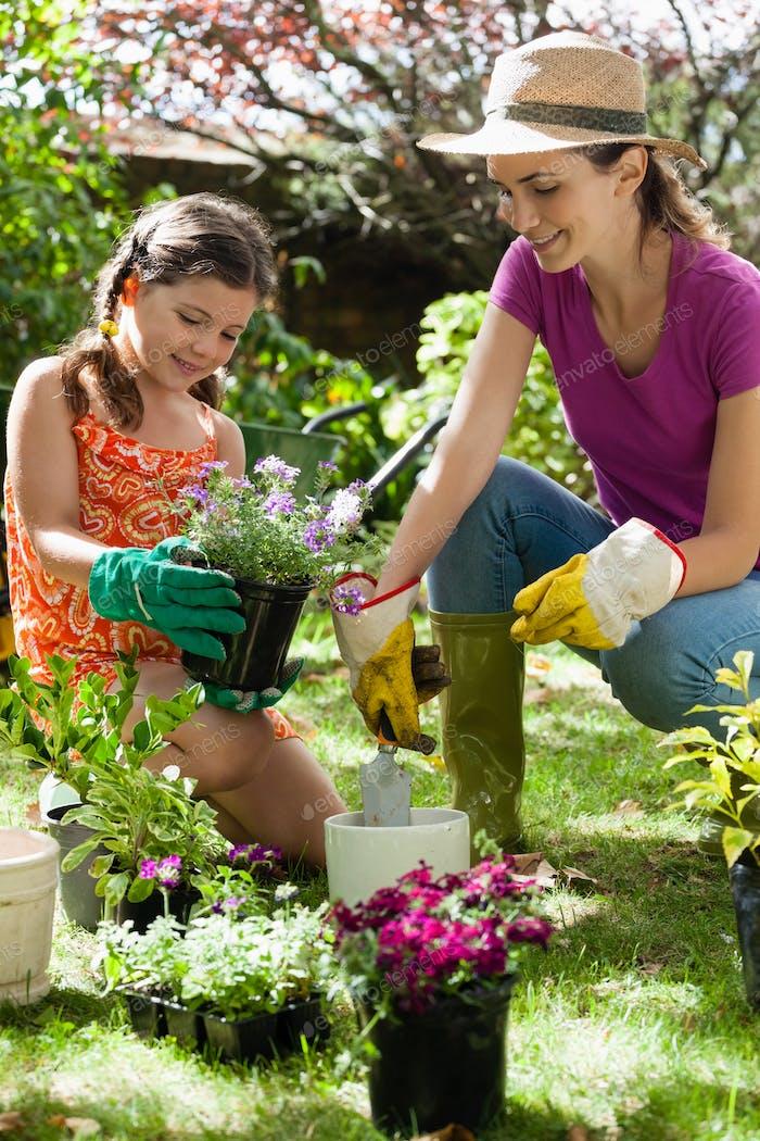 Mutter helfen Tochter in der Gartenarbeit am sonnigen Tag