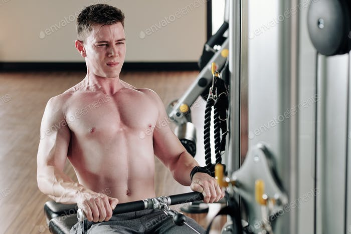 Man pulling cable of rowing machine