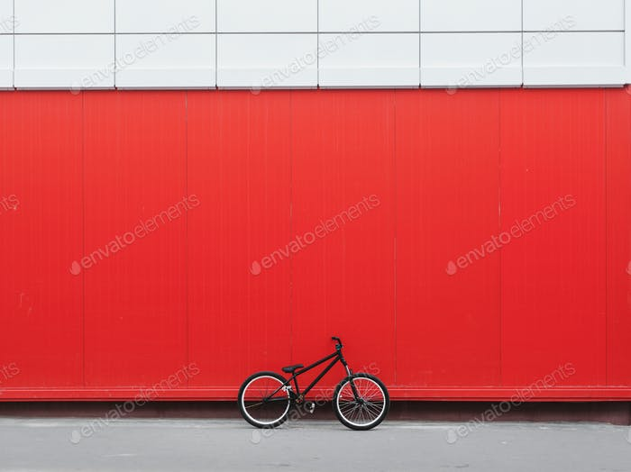 Bicycle leaning on red wall