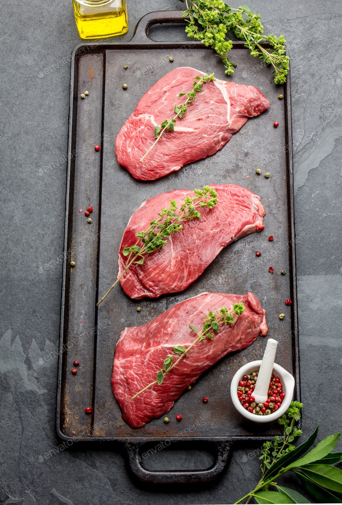 Raw Beef Steak with Herbs on Black Board