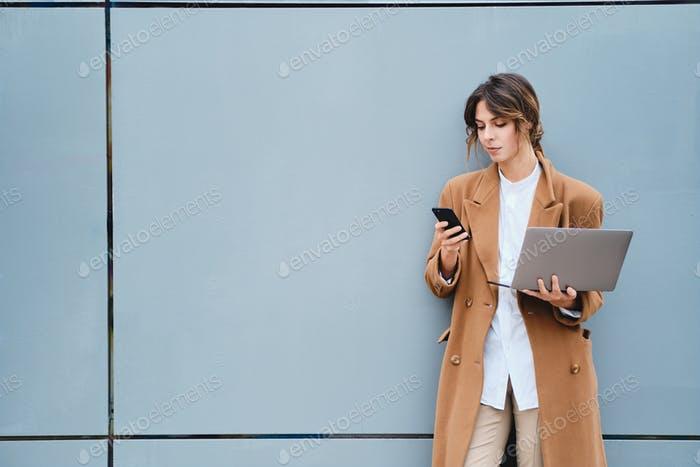 Young beautiful stylish businesswoman in coat with laptop confidently using cellphone outdoor