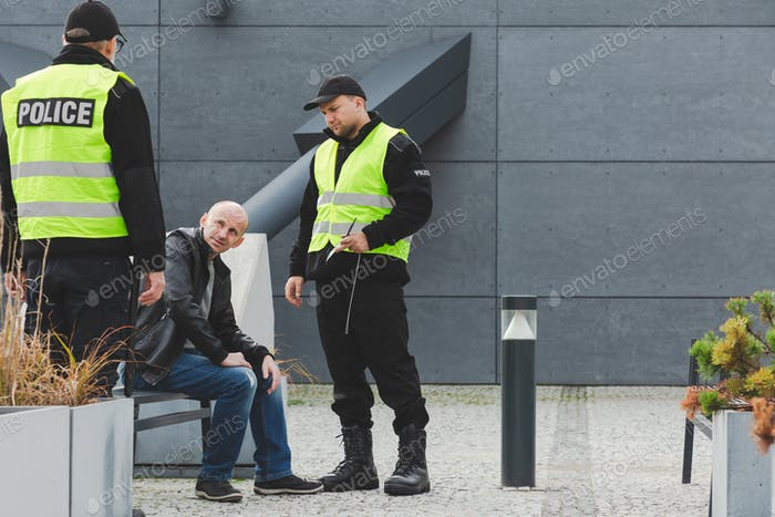 Police officers during patrol next to homeless man sitting on the bench in the city