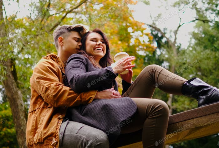 Пара сидит на деревянном мосту в осеннем парке