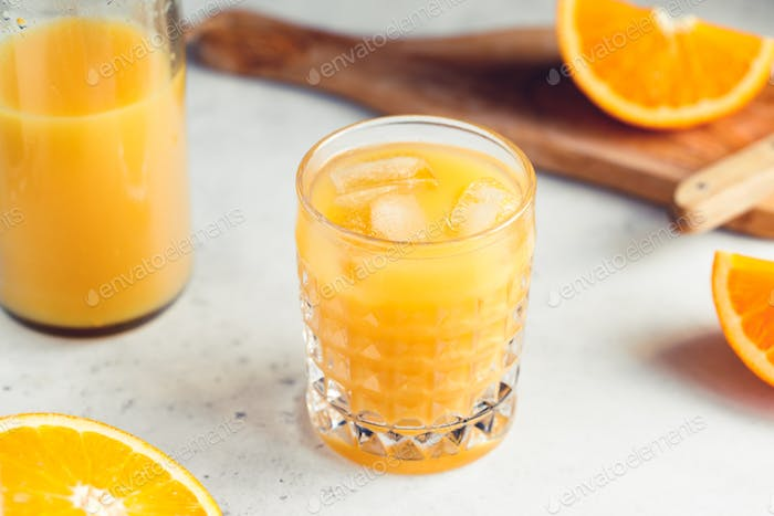 Fresh orange juice with ice cubes in a glass on a table. The concept of healthy eating.