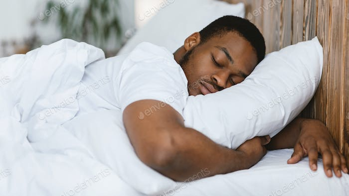 African Man Sleeping Hugging Pillow Lying In Bed At Home