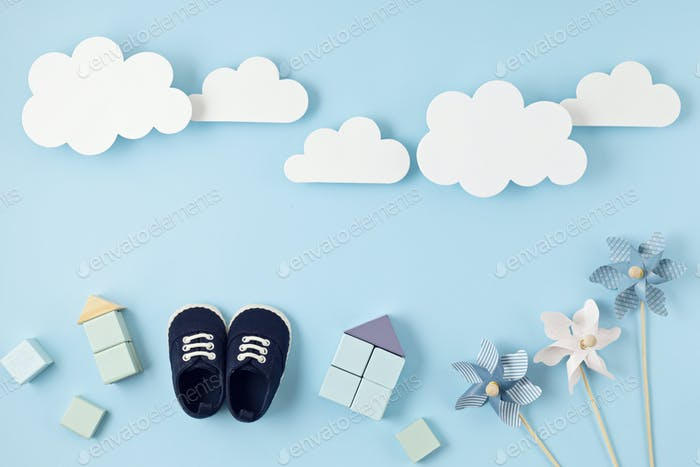 Cute newborn baby boy shoes with festive decoration over blue background. Baby shower, birthday