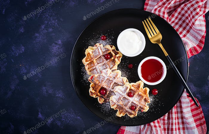 Traditional belgian waffles with berries, sour cream and jam on dark table. Top view, overhead