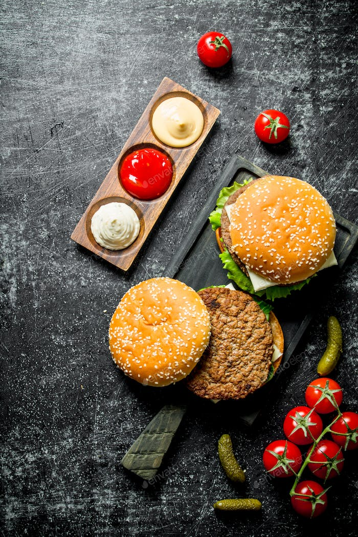 Burgers with French fries, gherkins,tomatoes and different sauces.