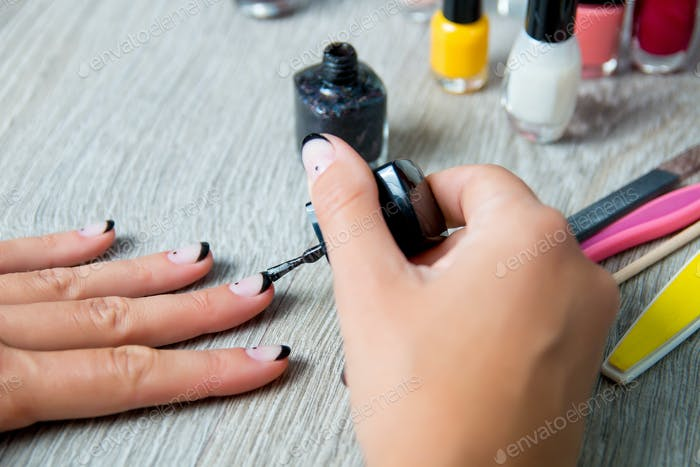 Black nail polish being applied to hand with tools for manicure on background.