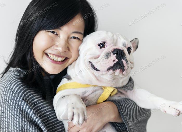Asian woman hugging dog