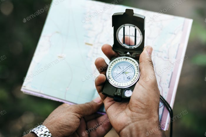 Hand holding compass and a map
