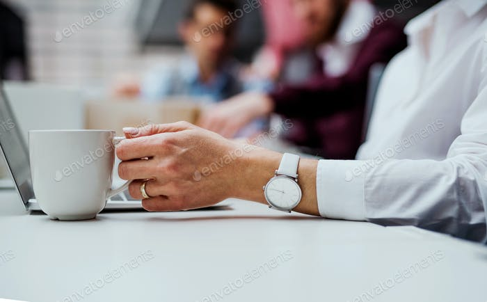 A midsection of businesswoman with a cup of coffee working in office, using laptop.