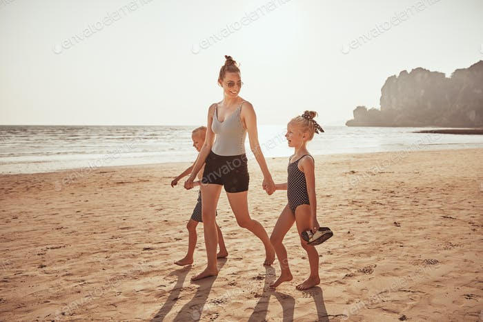 Smiling Mother and children walking together along a sandy beach