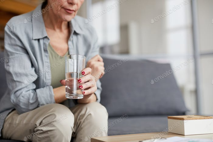 Worried Mature Woman Drinking Water