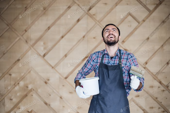 Man with tin of paint and brush looking up on a wooden wall background