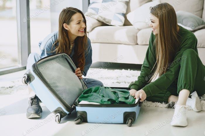 Women prepare travel suitcase at home