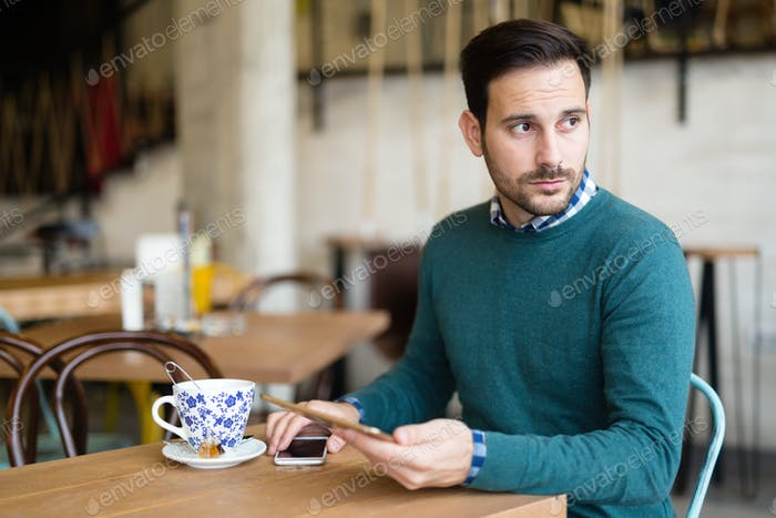 Portrait of young attractive man using tablet