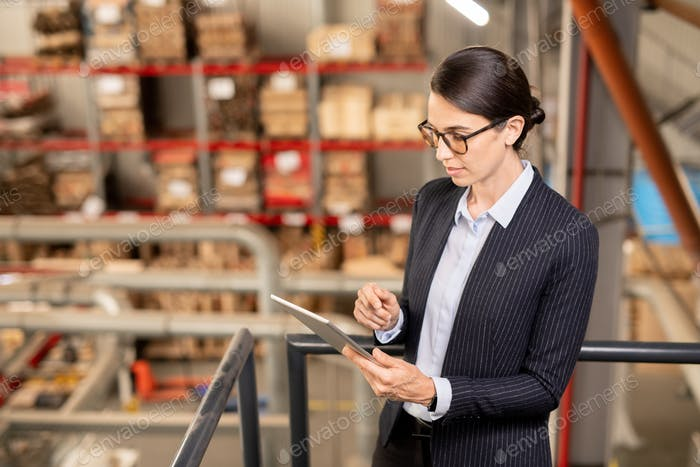 Young expert of industrial plant scrolling in tablet while surfing in the net