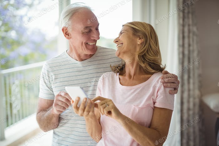Happy senior couple using mobile phone in balcony