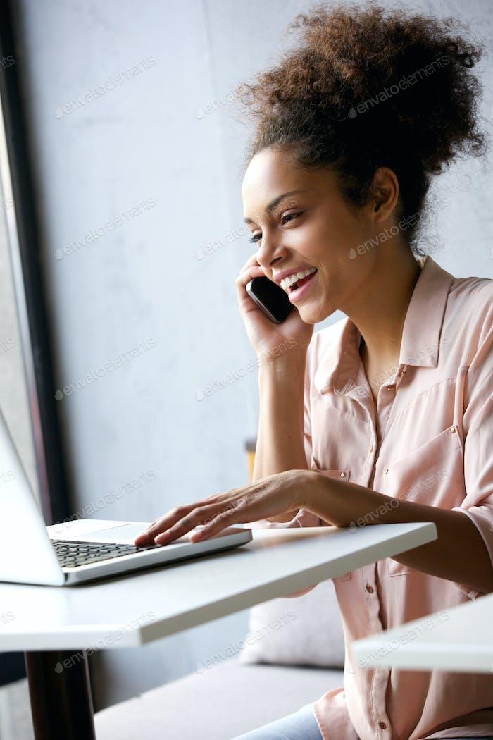 Junge Frau im Gespräch am Telefon und Blick auf Laptop