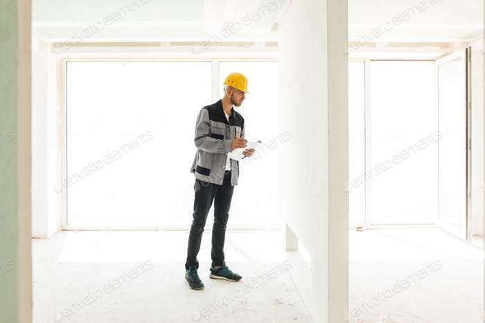 Young engineer in work clothes and yellow hardhat holding plan o