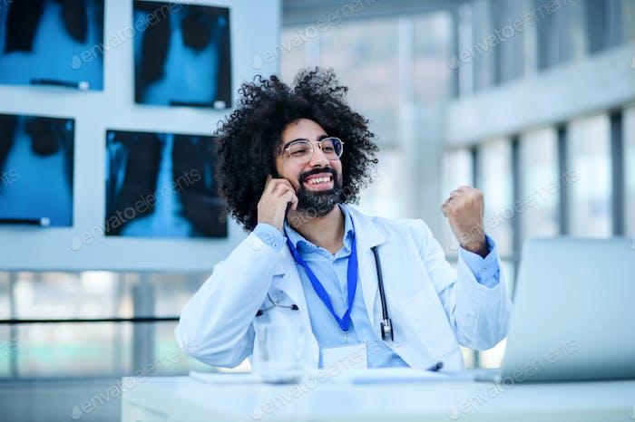 Porträt des männlichen Arztes sitzt im Krankenhaus, mit Laptop und Smartphone