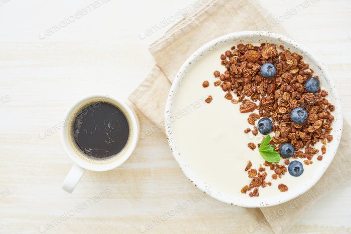Yogurt with chocolate granola, bilberry. Breakfast with cupof coffee on a white background