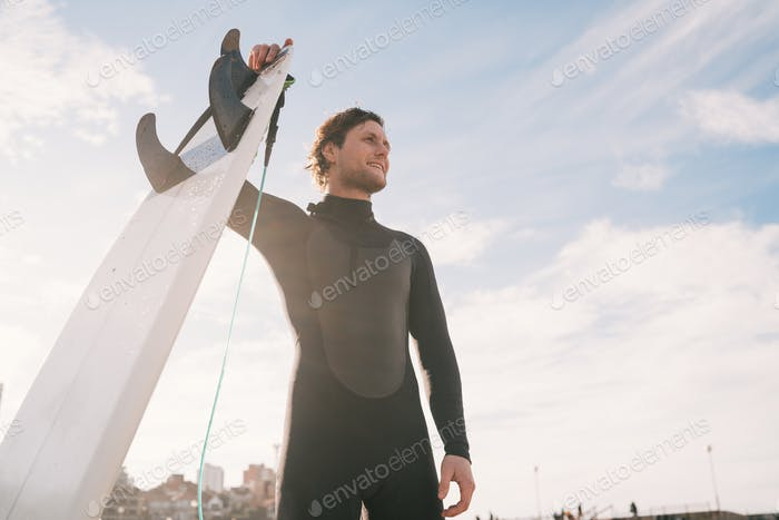 Surfer standing at the beach with surfboard.