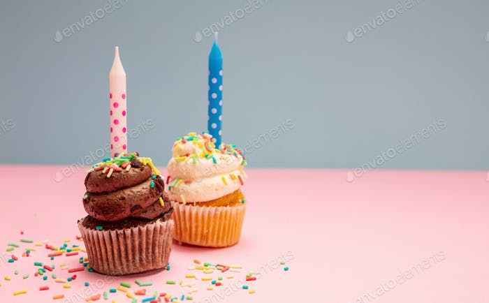 Two birthday cupcakes with candles on blue and pink pastel background, copy space.