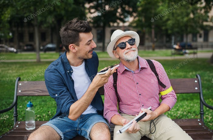 Young man and blind senior sitting on bench in park in city, using smartphone.