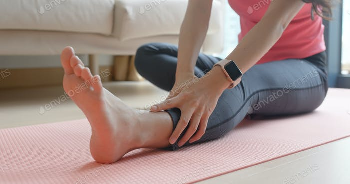 Woman stretching legs at home