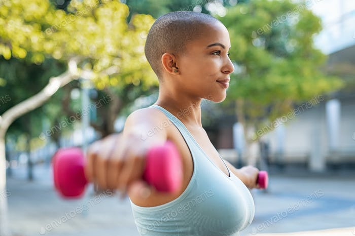 Curvy black woman using dumbbell