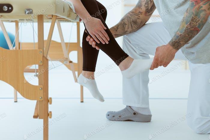 Physiothérapeute touchant le pied blessé d'un patient