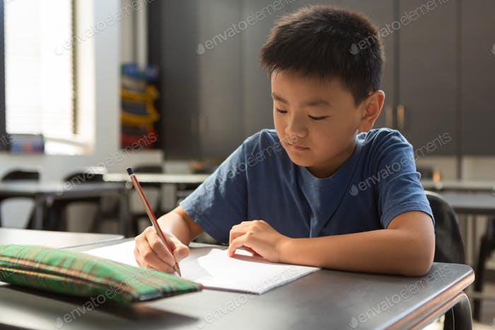 Front view of Asian schoolboy writing on a book at desk in classroom at elementary school