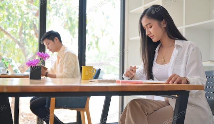 Frauen und Männer arbeiten im Café.Sie sitzen in sozialer Distanzierung.