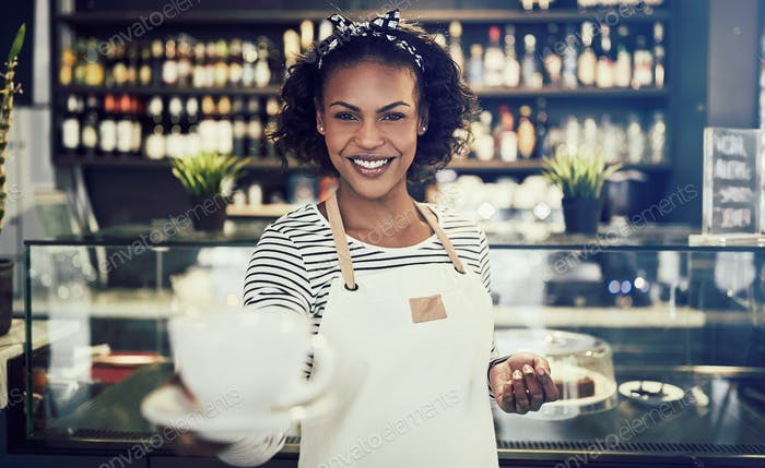 Smiling cafe waitress offering up a cup of coffee