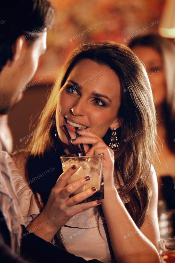 Beautiful Woman at the Bar Talking with a Guy