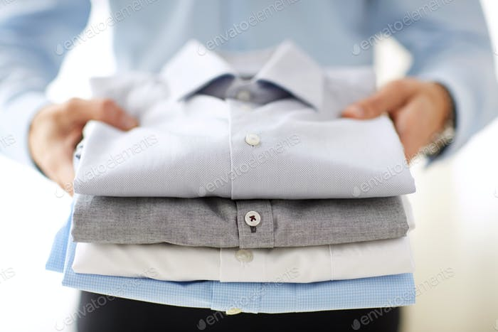 close up of businessman holding shirts