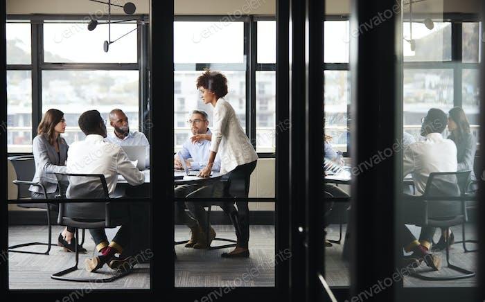Millennial black businesswoman stands addressing colleagues at a meeting, seen through glass wall