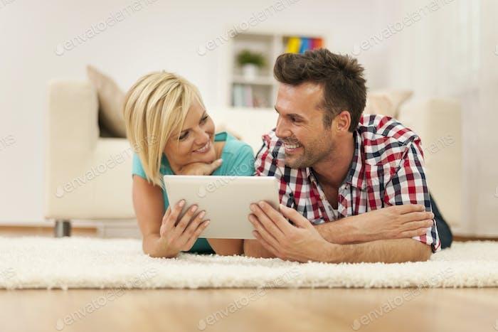 Flirting couple using digital tablet on carpet in living room