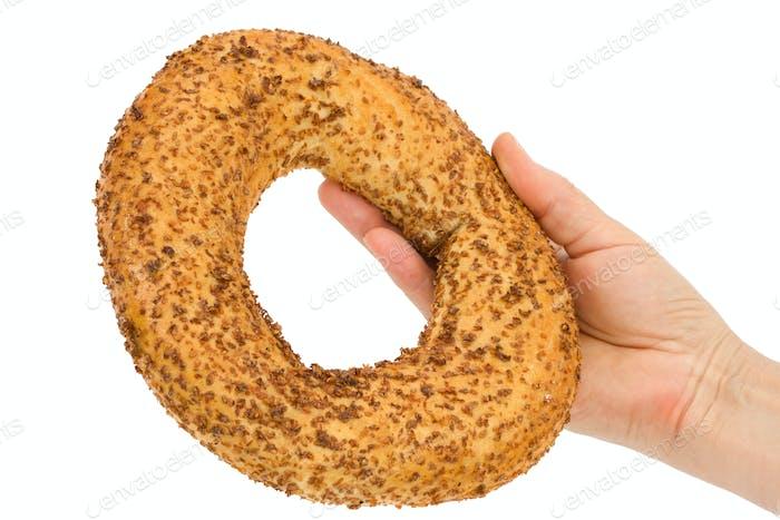 Female hand holding fresh bagel, isolated on white background