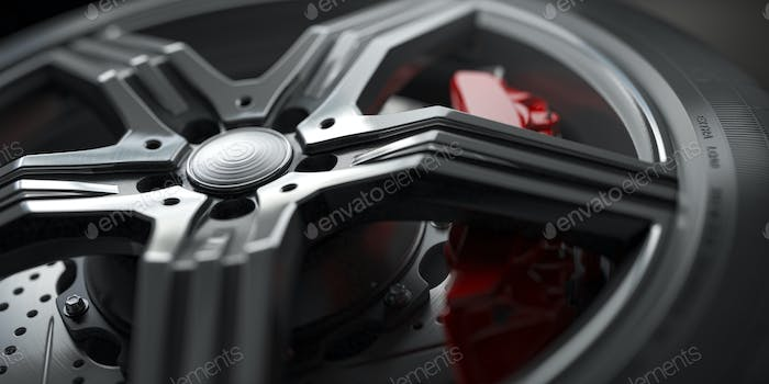 Alloy car wheel with disk brakes close up background.