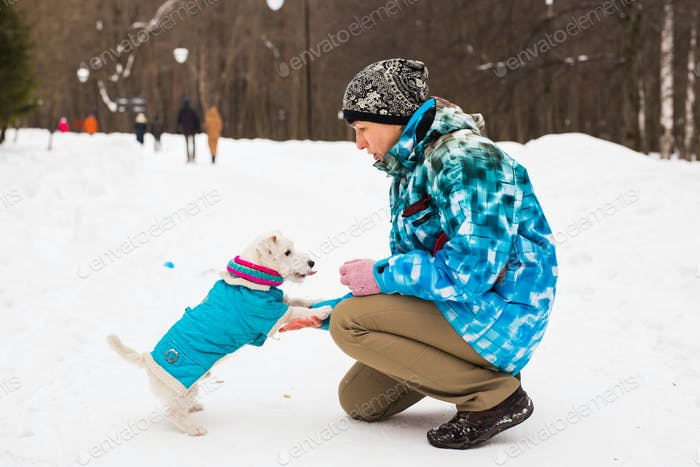 Middle aged woman outdoors with cute dog - Jack Russell Terrier in winter season